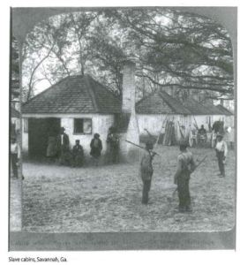 Historical black and white photograph of several African American people standing and leaning against a few small white brick structures.