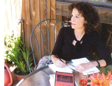 Julia Alvarez sitting in a chair outside with a notebook in front of her.