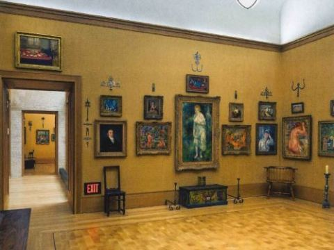 Multiple paintings and portraits hang in a light brown room.