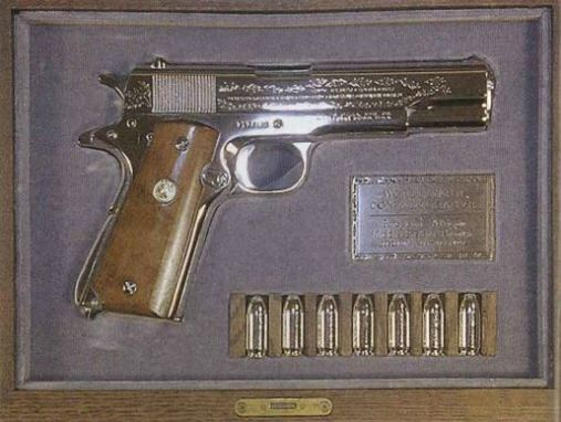 Image of a handgun on display in a velvet lined box with six bullets also on display.