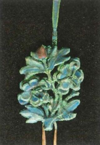 Green efflorescent deposits appear on Chinese decorative enamel and silver objects.