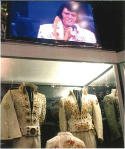Image of a case at Graceland with two of Elvis' white with gold sequin jumpsuits.