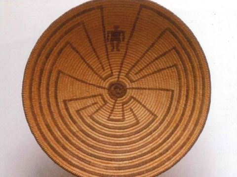 Brown woven basket with a tribal design. The design depicts a man going through a maze.