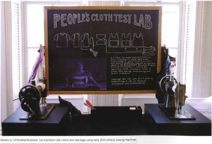"View of two sewing machines with a chalkboard text panel in between them that reads ""People's Cloth Test Lab""."