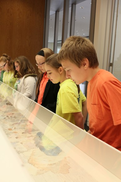 Five middle school students look down into an exhibit case.