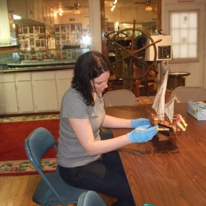 A woman sits on a folding chair at a folding table wearing Nitrile gloves and holding a model sailing ship in her hands.