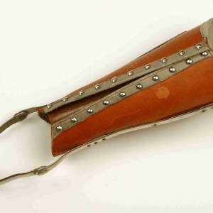 Leather contraption with metal trim and an ankle strap.