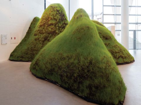 Four mounds of grass sit directly on the floor in an interior exhibition space.
