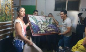 A Hispanic woman and three Hispanic men hold up a piece of framed art with angels in it.