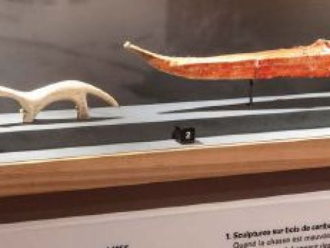A model boat and a carved bone animal sit in a display case.
