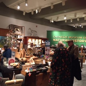 Interior view of the Carnegie Museum of Natural History's Museum store with a few people shopping.