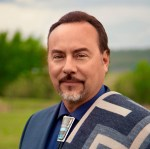 Headshot of a dark-haired man standing outside with a goatee wearing a geometric style blanket on one shoulder and a bolo tie.
