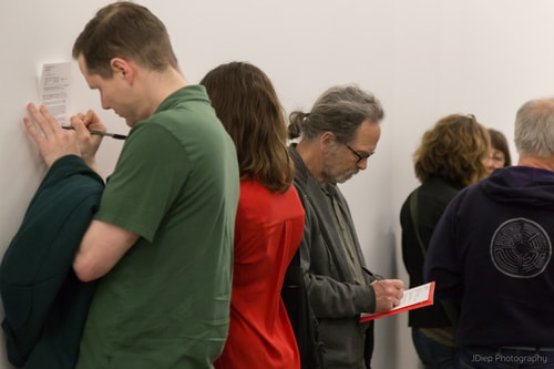 People stand huddled writing on pieces of paper.