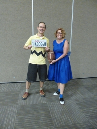 Phil Kohlmetz wears a handmade recreation of Charlie Brown's famous outfit: a yellow polo shirt with a zigzag across the waist, black shorts, and brown shoes. He holds one of the Snoopy license plates. Shawn Lum recreates Lucy's standard outfit with a blue dress and black-and-white saddle shoes, and holds a football, a reference to a famous Peanuts tableau.