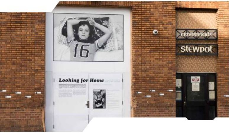 View of a brick wall with several text and image panels showing various people experiencing homelessness.