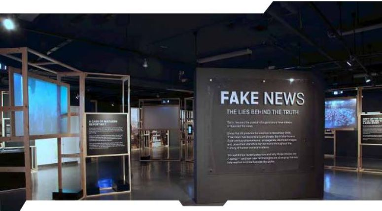 Image of the interior of a very darkly painted exhibition on Fake News.