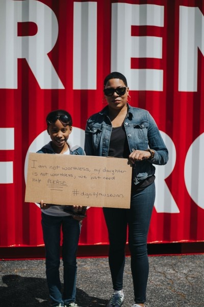 "A woman and a child stand in front of the museum holding a cardboard sign that says ""I am not worthless, my daughter is not worthless, we just need help PLEASE. #DignityMuseum"""