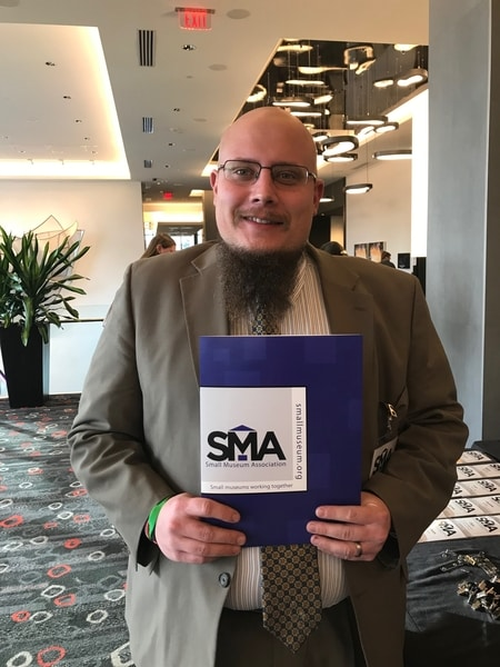 A man in professional dress stands in the lobby of a meeting space holding a folder with the Small Museum Association logo on it.