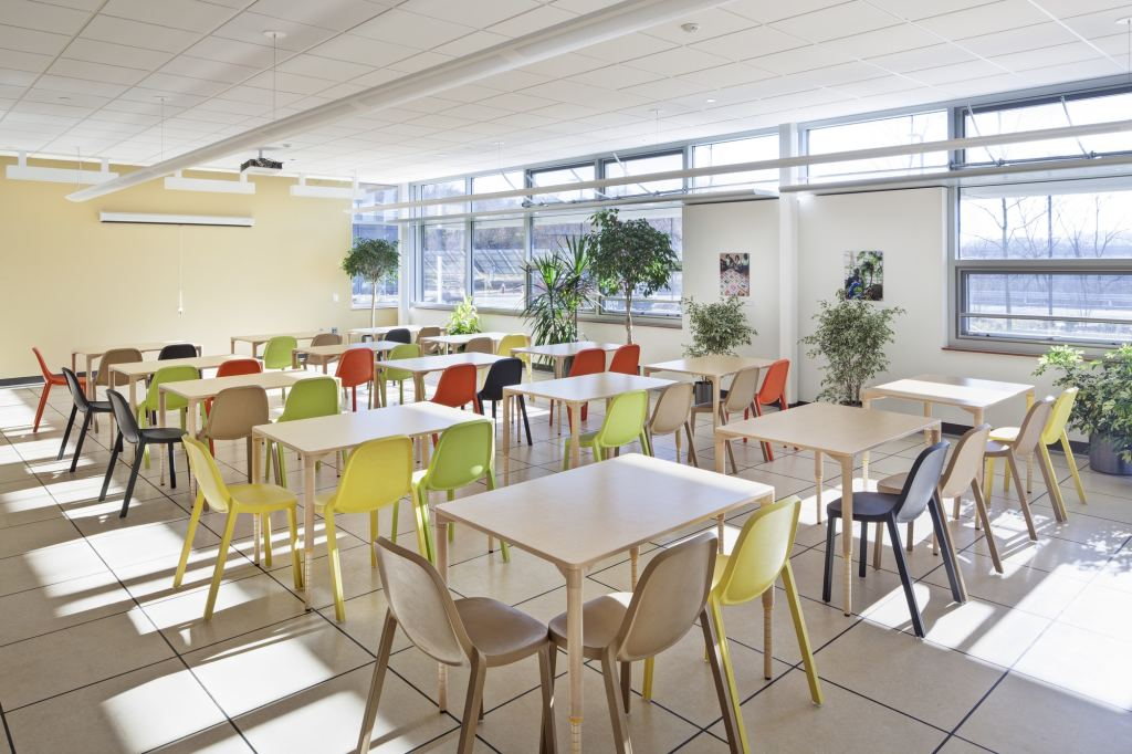 A naturally lit room with tables surrounded by chairs of different colors, including bright yellows and greens.
