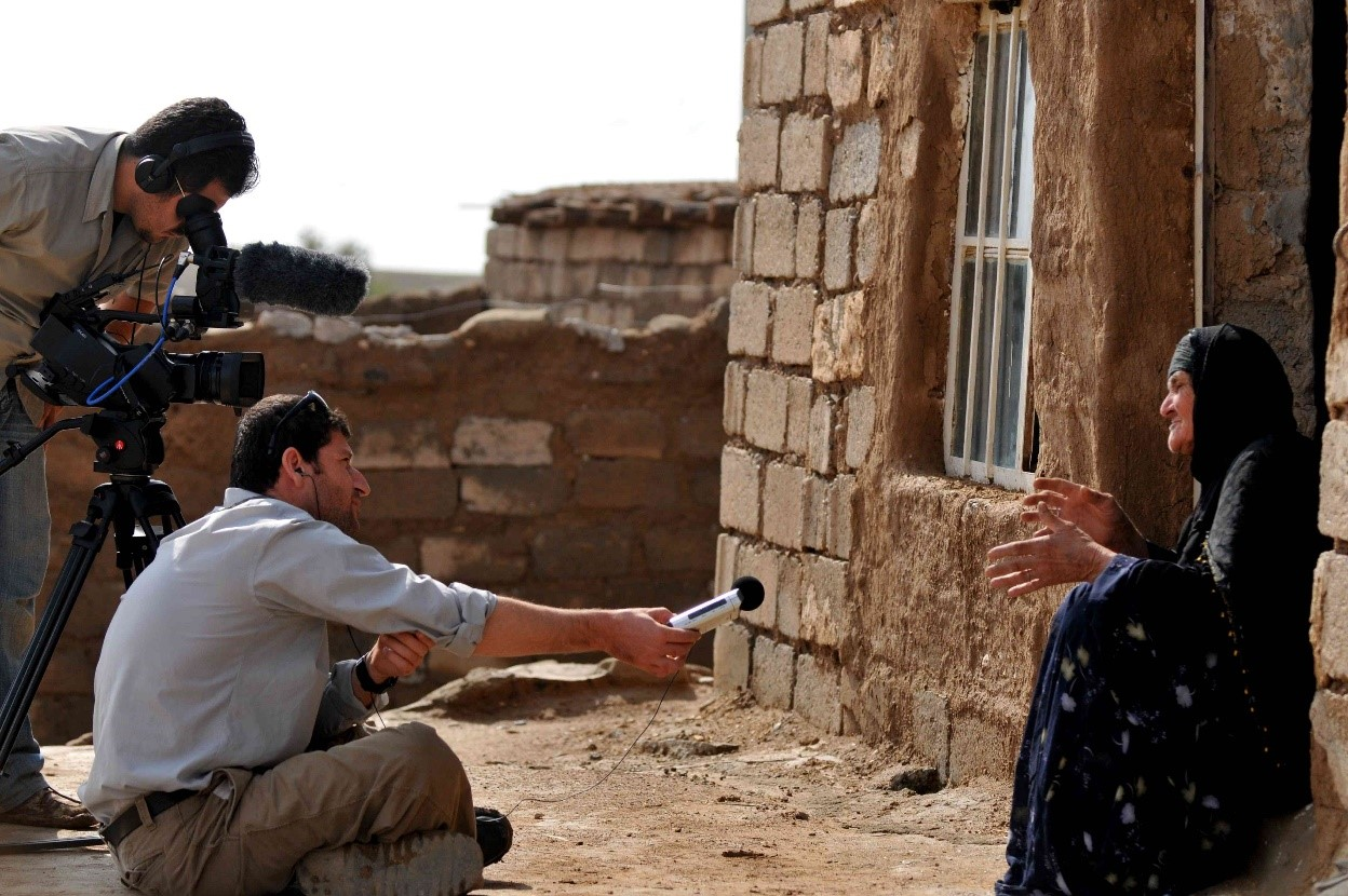 A man holds a microphone toward a woman while a camera operator films her next to him. The woman is wearing traditional Kurdish clothing and sitting in front of a traditional house. The men are in Western clothing.