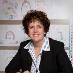 Image of Carole Charnow, a white woman sitting in front of a wall with children's drawings wearing a dark suit jacket and striped shirt.