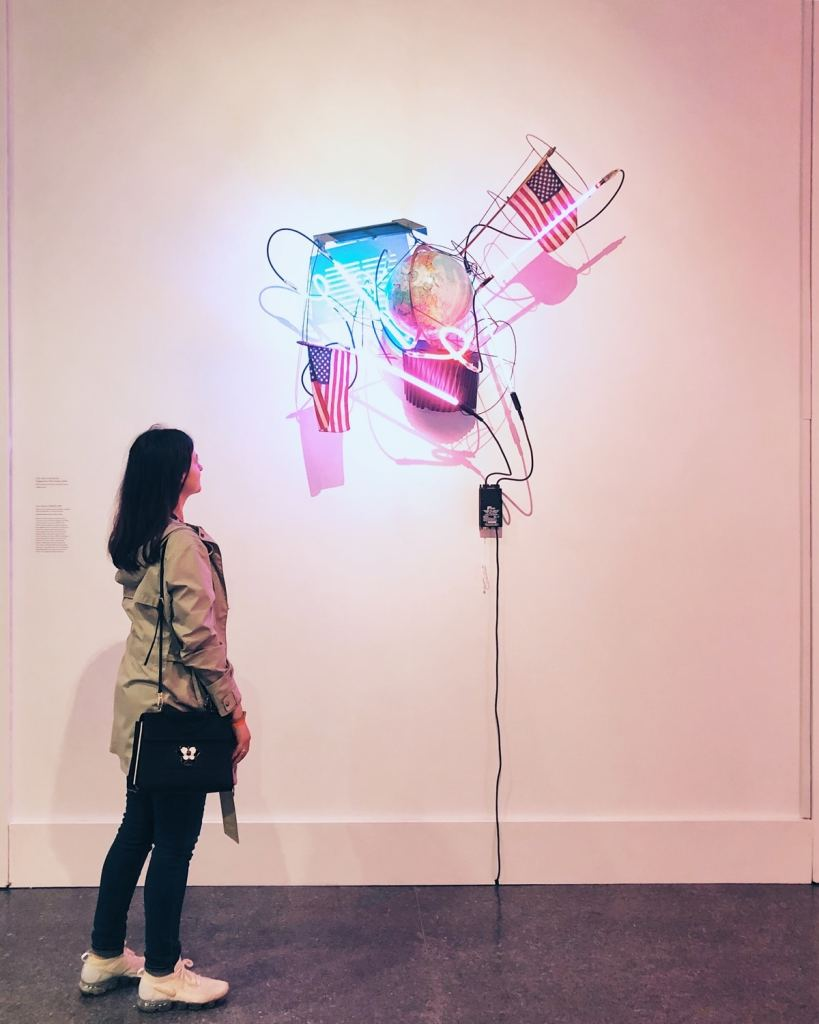 The author stands next to a sculpture made of neon tubes and handheld American flags, among other things.