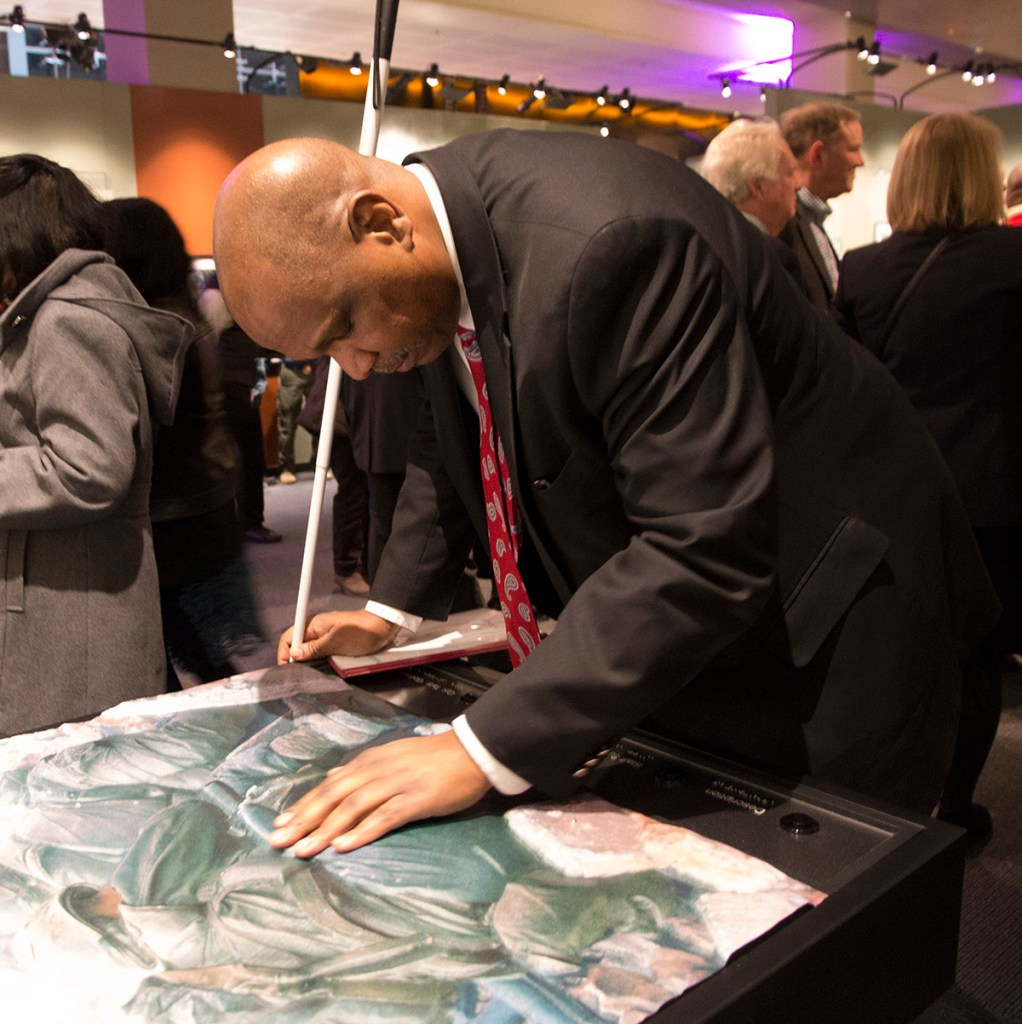 A man holding a cane leans over a tactile print on a table with his hand placed on its raised surface.