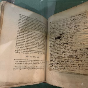 An open copy of an antique book on display, with handwritten annotations visible.