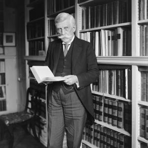 A black-and-white portrait of Oliver Wendell Holmes standing in a library and holding a book.