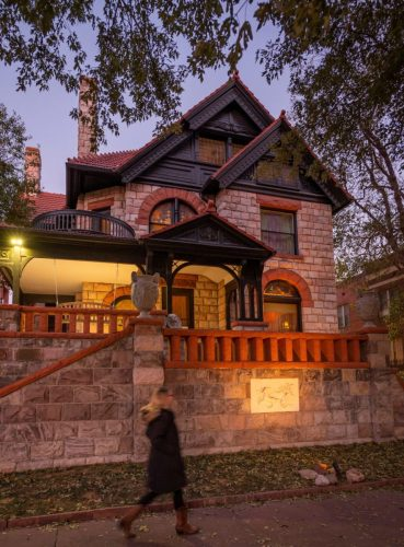 The outside of a historic Victorian home seen at dusk.