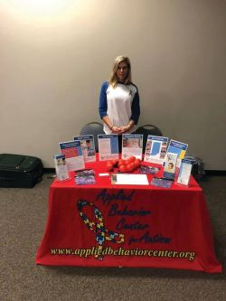 A woman stands behind a table with various pamphlets on top.