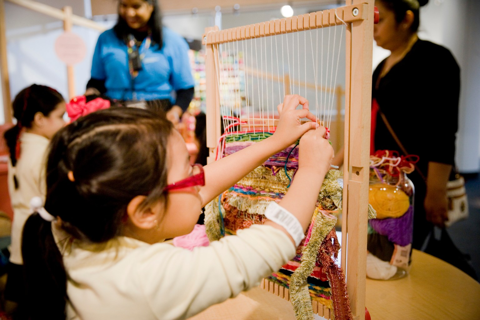 A young child experiments with weaving in a museum space.