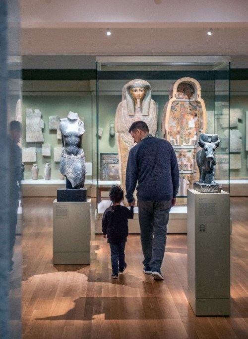 An adult and child tour a gallery of Ancient Egyptian artifacts.