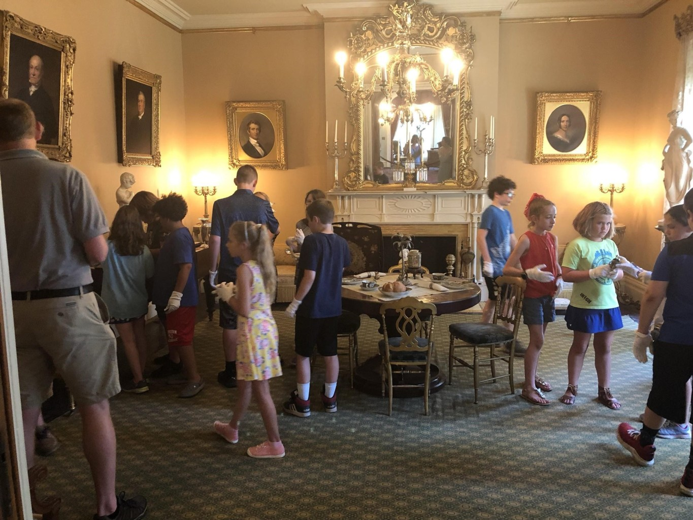 A group of campers wearing white gloves explore the interior of a historic house.