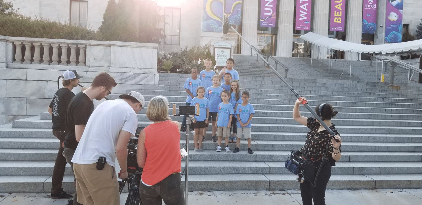 A film crew records a group of children on the aquarium's steps.