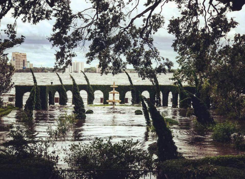 The garden is seen submerged in water, with only a few trees and architectural features visible.