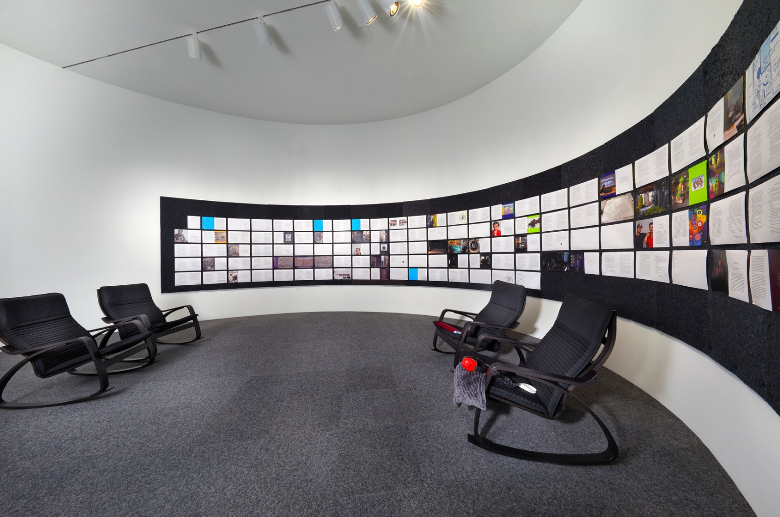 In a room with curved walls, rocking chairs are arranged in front of a grid of images.