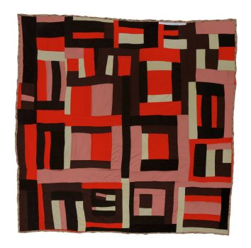 A quilt made up of curving, irregular strips of red, black, and grey fabric.