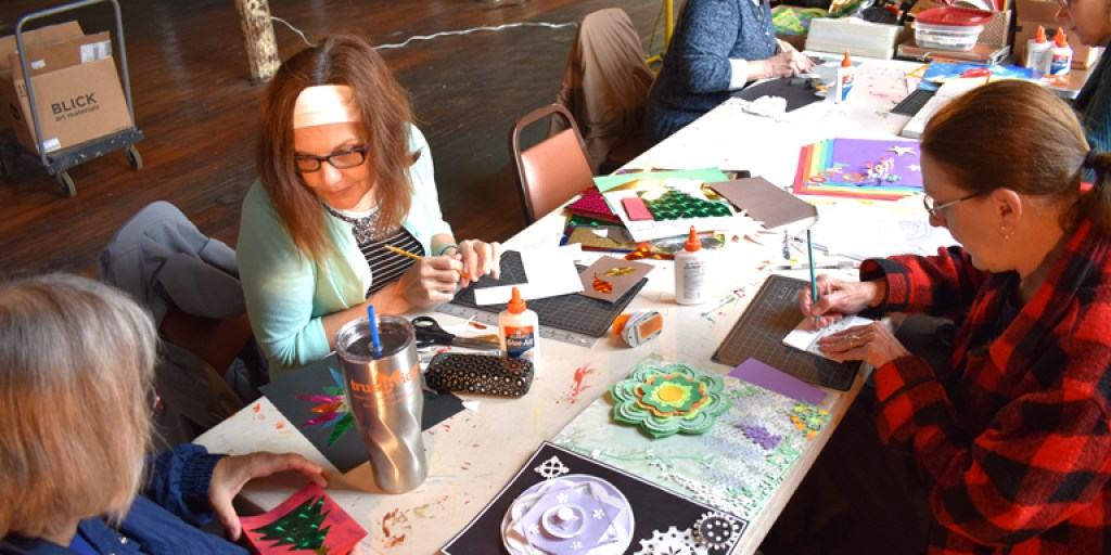 Participants sit around a table working on cut paper projects, with some motifs reminiscent of wheels.