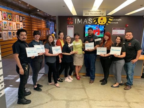Staff members of the IMAS gather around the admissions and membership desk of the museum, holding up signs that say messages of welcoming in multiple languages.