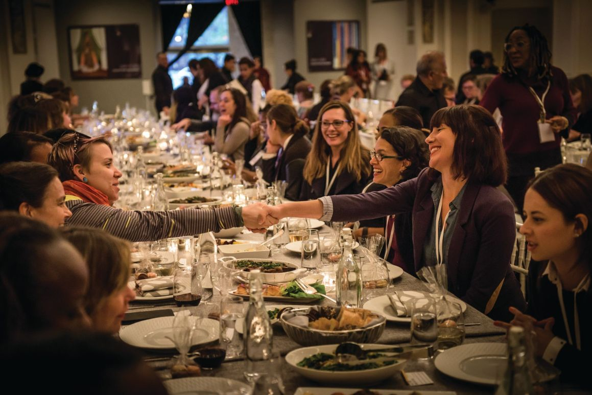 Two women shake hands across a long table where a large group of people sit down for dinner.