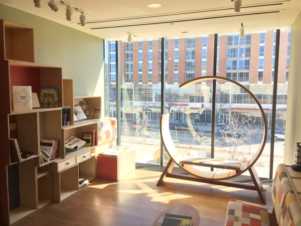 A round wood chair and modular shelves next to a floor-to-ceiling glass window