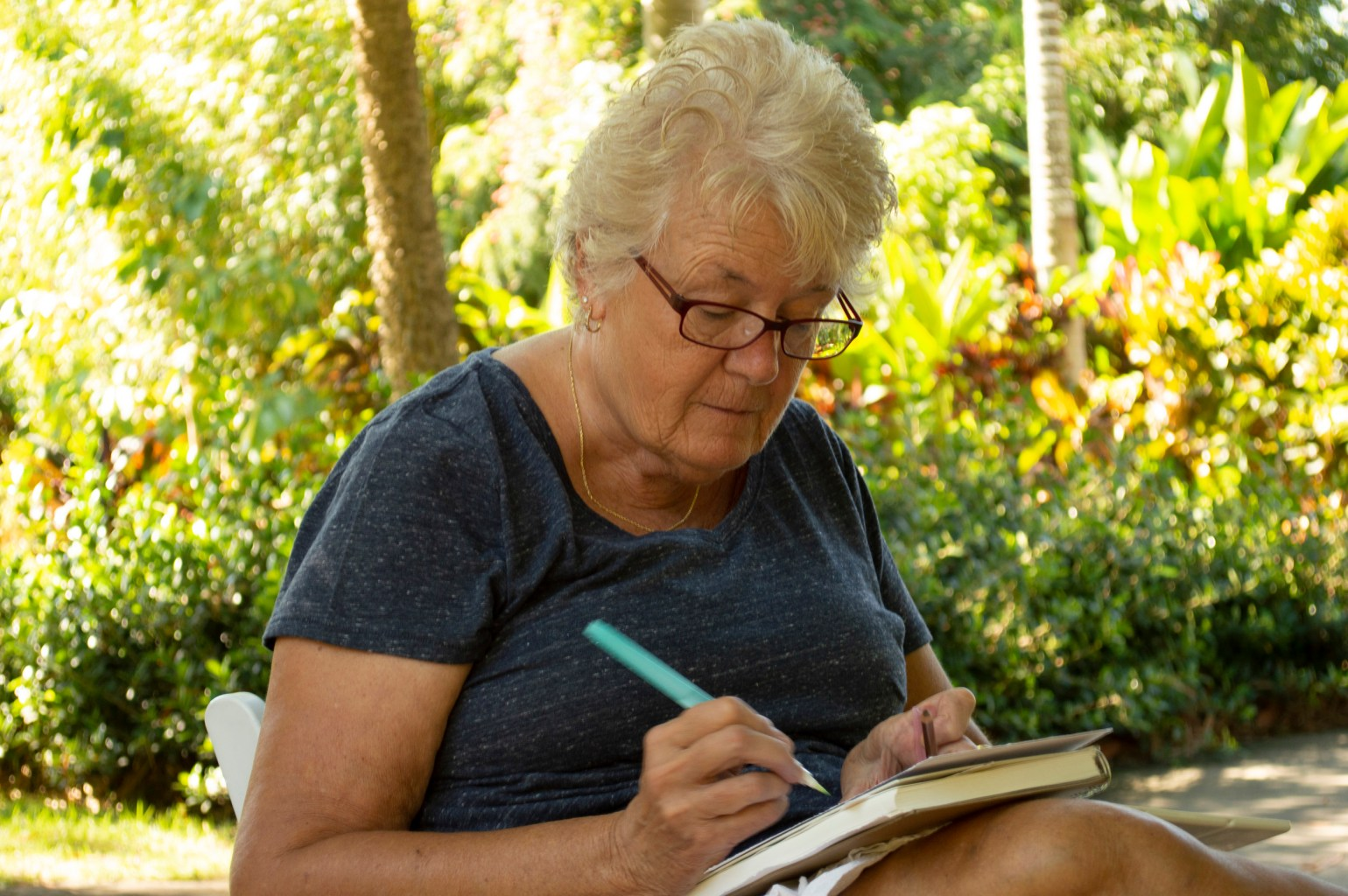 A person in a garden concentrating on a piece of paper with a drawing implement in hand
