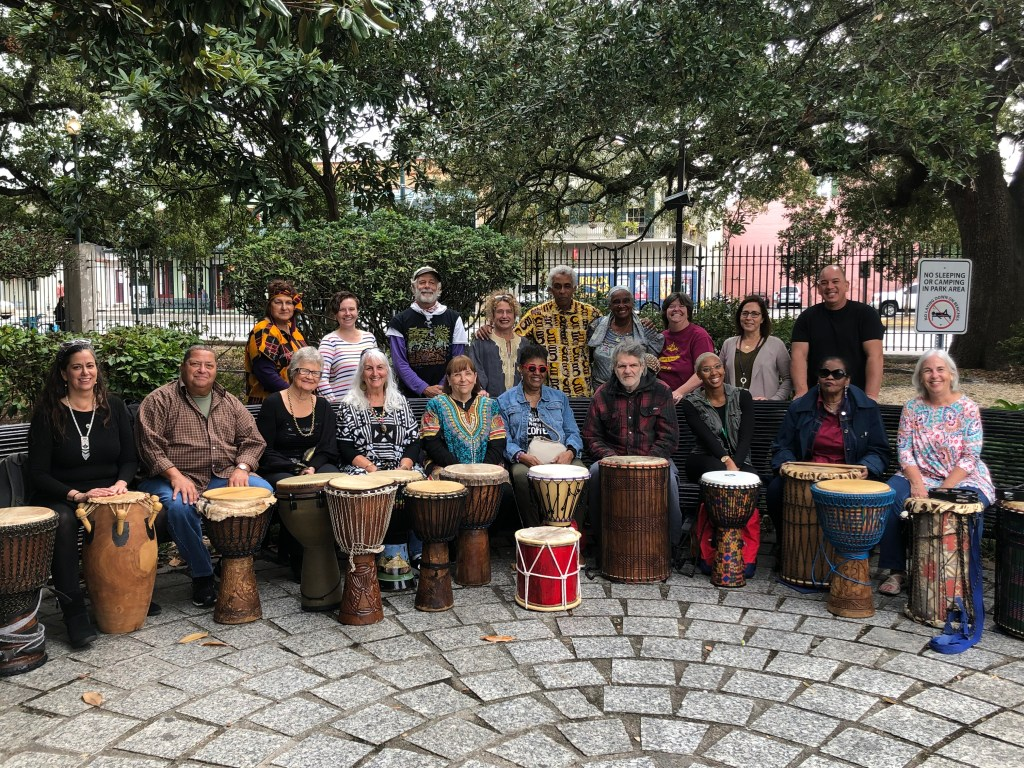 Participants posing for a large group portrait in front of standing drums
