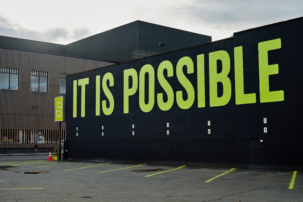 """A black-painted building with bright green lettering reading """"It is Possible"""""""
