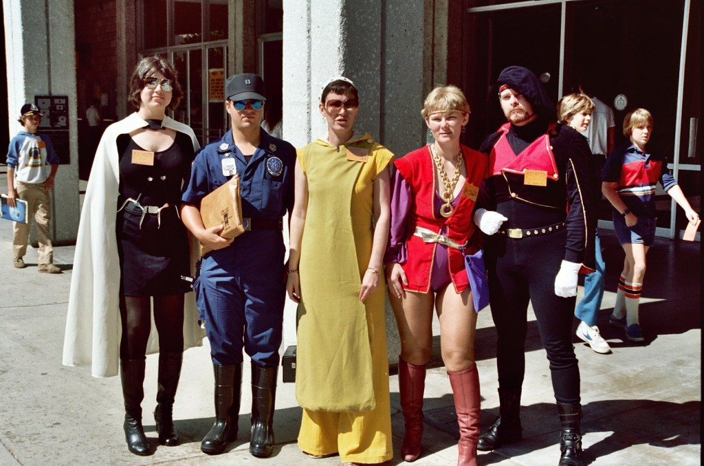 A group of people wearing a variety of costumes outside of a convention center