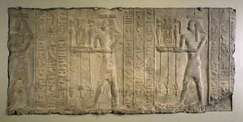 A carved relief showing human figures next to hieroglyphic symbols