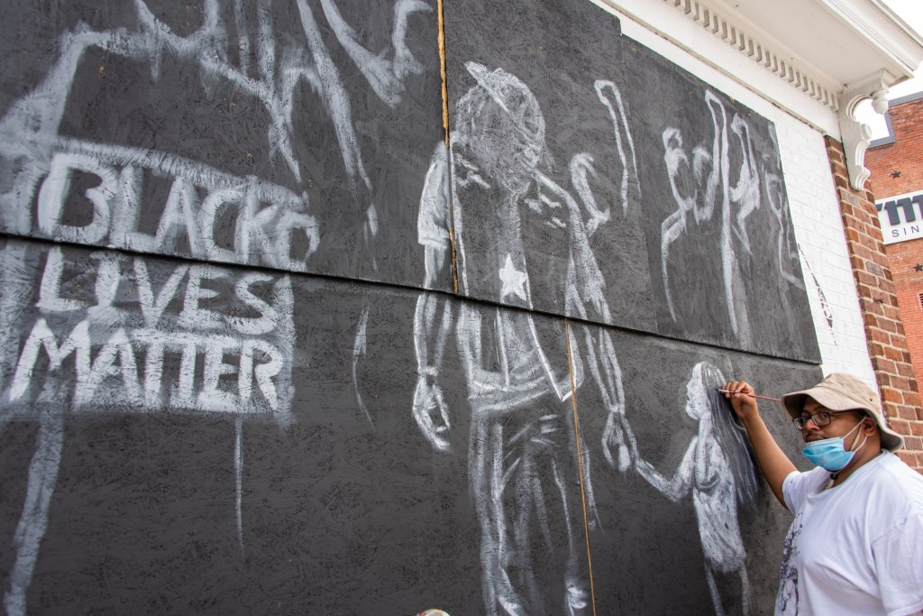 An artist holding a paintbrush working on a mural depicting a Black Lives Matter protest in a loose, minimal style