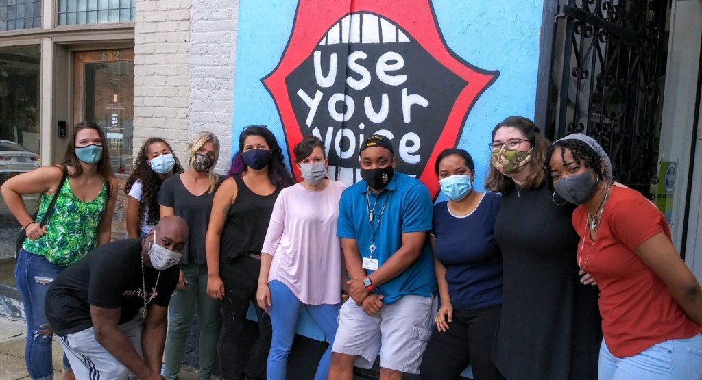 """A group of people posing in front of a mural depicting an open mouth with the message """"Use Your Voice."""""""