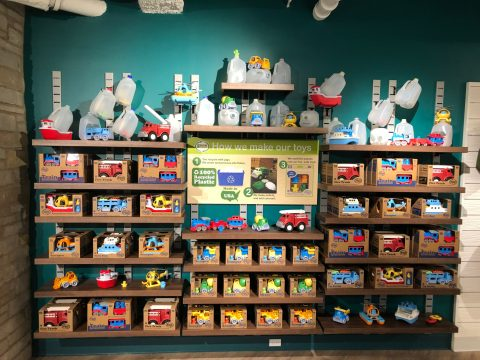 """A wall of toys displayed with a sign reading """"How we make our toys"""" explaining they are made of 100 percent plastic."""